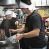 熱気に包まれたラーメン屋の厨房の写真