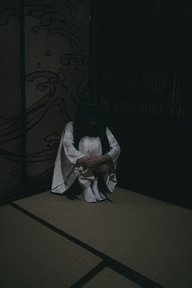 縮こまる白装束の女性の写真