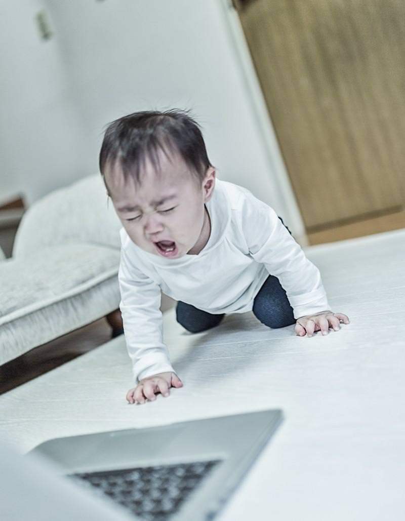 MacBookの前で泣き叫ぶ赤ちゃんの写真