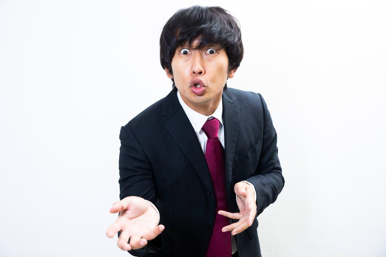 熱弁するスーツ姿の男性の写真